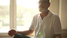 Man in the lotus position sits on the floor opposite the window. Elderly yogi, meditation and spiritual practices