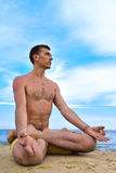 Man in lotus position Stock Images