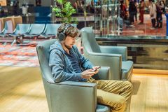 A man in the lounge area at the airport is waiting for his plane, uses a smartphone and headphones. Young smiling man stock image