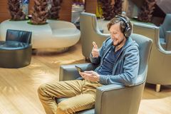 A man in the lounge area at the airport is waiting for his plane, uses a smartphone and headphones. Young smiling man stock photo