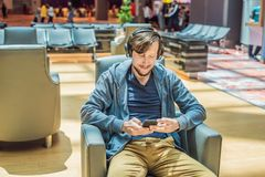 A man in the lounge area at the airport is waiting for his plane, uses a smartphone and headphones. Young smiling man stock photography