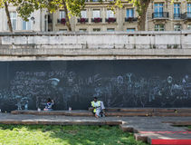 Man lounges and child draws at public chalk board, Paris Royalty Free Stock Photos