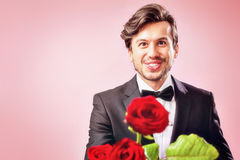 Man in love with a bouquet of roses. Man in love with roses smiling friendly Royalty Free Stock Photo