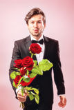 Man in love with a bouquet of roses. Man in love with roses showing a pout Stock Photos