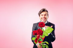 Man in love with a bouquet of roses. Happy man in love with roses Royalty Free Stock Image