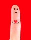 Man in love concept - a man with red heart, painted at finger is Royalty Free Stock Image