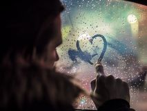Man in love drawing heart on window. E view of romantic man drawing heart on steamy car window against night lights Stock Photography