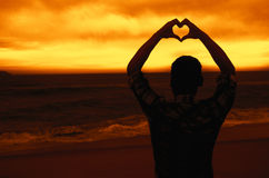 Man in love forming heart at beach at sunset Royalty Free Stock Photography