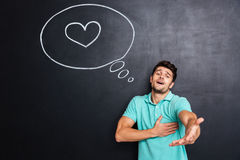 Man in love giving you his hand over chalkboard background. Handsome young man in love giving you his hand over chalkboard background with heart drawn in speech royalty free stock photos