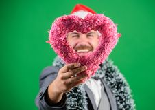 Man in love happy wear santa hat celebrate christmas green background. Spread love around. Merry christmas and happy new. Year. Hipster hold heart symbol of stock image
