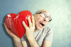 Man in love holds a red heart shape pillow. Blue background Royalty Free Stock Photography