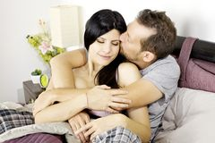 Man in love kissing wife in bed Stock Image