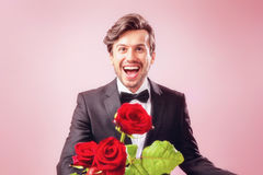 Man in love overjoyed with bunch of roses royalty free stock photography