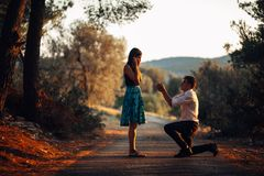 Man in love proposing a surprised,shocked woman to marry him.Proposal, engagement and wedding concept.Betrothal.Being affianced. To love of life.Kneeling Royalty Free Stock Images
