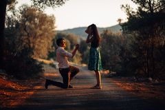 Man in love proposing a surprised, shocked woman to marry him at sunset. Proposal, engagement and wedding concept. Betrothal royalty free stock photos