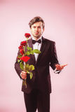 Man in love with roses in hand. Man in love with roses showing a pout Stock Images
