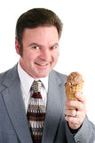 Man Loves Chocolate Ice Cream. Handsome businessman excited about eating chocolate ice cream from a waffle cone. Isolated on white background royalty free stock photography