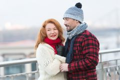 Man loves rude woman closing his eyes. Guy in rad jacket and scurf happy to woman in red scurf. Aged couple meet in city. Man loves red hair woman closing his Stock Image