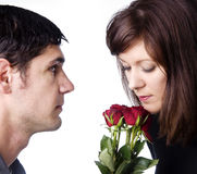 Man lovingly giving red roses to his wife. Stock Image