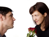Man lovingly giving red roses to his wife. Royalty Free Stock Image