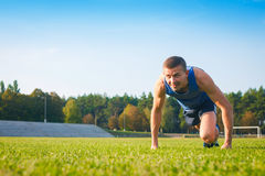 Man in low start position on old stadium. Athlete in starting position. Running, jogging, cardio, sport, active lifestyle concept Stock Photography