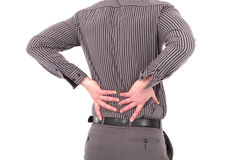 Man with lower back pain. Or backache caused by injury, stress or bad posture holding his back with both his hands, cropped torso portrait on white Stock Images