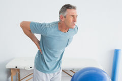 Man with lower back pain at the gym hospital. Mature man with lower back pain standing in the gym at hospital Royalty Free Stock Image