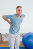 Man with lower back pain in the hospital gym. Mature man with lower back pain standing in the gym at hospital Stock Images