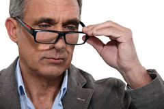 Man with lowered glasses Royalty Free Stock Photography