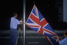 Man lowering British Union Jack flag in Hong Kong Royalty Free Stock Images