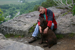 Man and Loyal Dog on Mountain Peak. A man and his loyal Chocolate Labrador Retriever dog sit on a mountain ledge in Upstate New York Royalty Free Stock Image