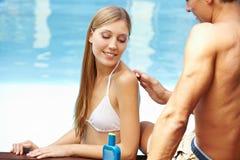 Man lubing back of woman Royalty Free Stock Image