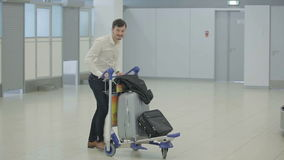 The man with luggage in the airport building. The action takes place at the airport building. The handsome young man carries his valise and suitcase by the stock video footage