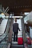 Man with luggage on escalator Royalty Free Stock Photo