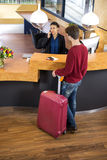 Man With Luggage At Hotel Reception Royalty Free Stock Photography