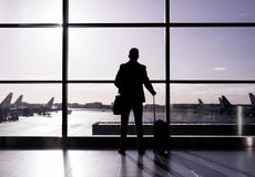 Man standing in airport, silhouette against glass wall. Man with luggage standing in airport, silhouette against glass wall Royalty Free Stock Photography