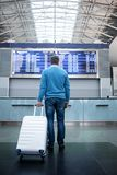 Man with luggage is waiting for flight in modern terminal. Lets travel. Full length back view of trendy tourist is standing in international airport with white Stock Image