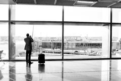 Man with luggage waiting hall of airport at window glass. Man, businessman guy or tourist passenger with suitcase and luggage waiting for flight in airport hall Stock Photo