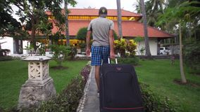 Man with suitcase settles in a hotel. Man with luggage walks through the hotel to the reception desk in the hotel. Tourist with suitcase in hotel lobby. Travel stock footage