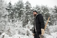 Man lumberjack in thermal jacket with ax. Man lumberjack with ax. Camping, traveling and winter rest. skincare and beard care in winter, beard warm in winter stock photos