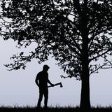 Man, lumberjack with an ax standing near a deciduous tree in the Royalty Free Stock Image