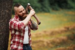 Man lumberjack with beard and moustache in red checkered shirt shaves with axe blade on natural background. Brutal man shaves. handsome strong serious man with royalty free stock photo