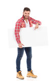 Man in lumberjack shirt holding blank placard and pointing Stock Photography