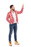 Man in lumberjack shirt pointing up Royalty Free Stock Photo