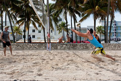 Man Lunges To Pass Ball In Miami Beach Volleyball Game. Miami, FL, USA - December 27, 2014:  A man lunges to pass the ball in a pickup game of beach volleyball Stock Photography