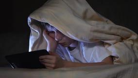 Man lurar genom att använda minnestavlaPC under filten på natten Pojken spelar dataspelar arkivfilmer
