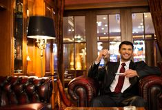 Man in luxury interior. Handsome smiling brunette sitting with a cup of coffee in a luxury interior Royalty Free Stock Photo