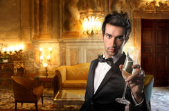 Man in a luxury room. Elegant man drinking wine in a luxury living room royalty free stock photos