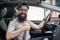 Man lyckliga le visningtummar för chauffören som kör upp sportbilen royaltyfria foton