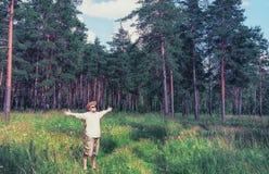 Man lyftta armar i skog Arkivfoto